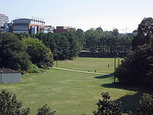 A grassy field surrounded by large, green-leafed trees and bushes. A sidewalk cuts through the field horizontally. A large red brick and white concrete building with idealized smoke stacks is in the background to the left, as are a few other less visible buildings.